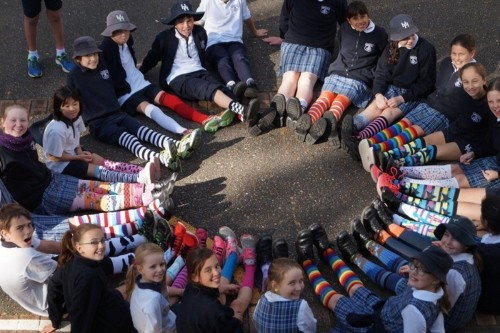 students in circle posing for picture and wearing different colourful socks